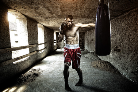 kick boxing: Young man boxing workout in an old building Stock Photo
