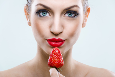 sweet tooth: Seduction - Beautiful eyed woman holding a strawberry  Stock Photo
