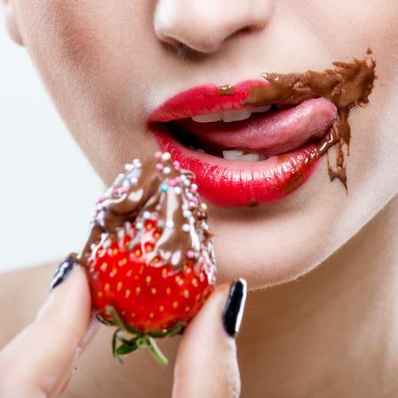 labios sexy: Seducci�n - rojo labios femeninos con la boca de chocolate, fresas sostienen Foto de archivo