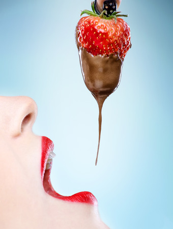 Seduction - red female lips eating chocolate strawberries photo