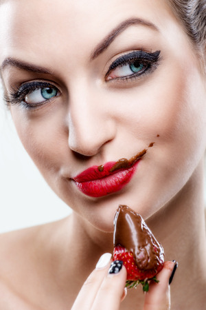 Attractive woman eating a strawberry, chocolate became the face of it  photo