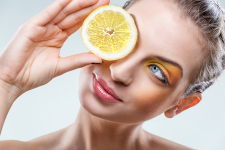 sexy food:  Beautiful woman with lemon and yellow makeup