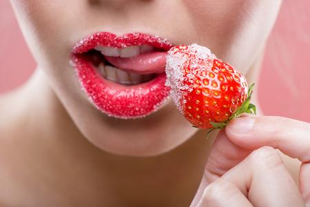 美しい女性の赤い唇、グラニュー糖とイチゴをなめる