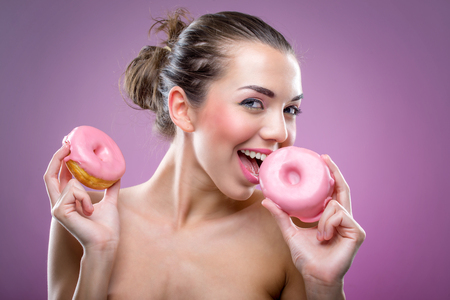 Beautiful woman with two donuts  You may eat or not  photo