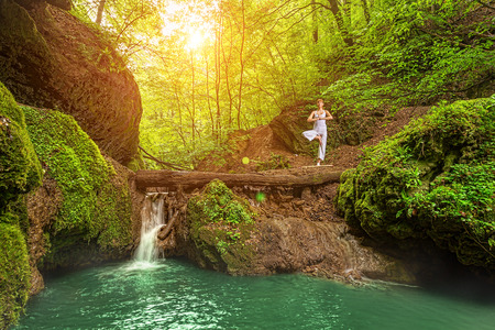 Still, relaxation, Woman practices yoga at the waterfall