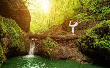 Woman practices yoga in nature, the waterfall