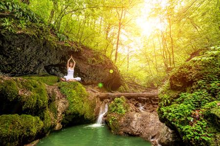 Woman practices yoga at the waterfall  Sukhasana pose