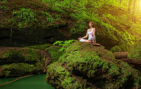 Relaxation in forest at the Waterfall  Ardha Padmasana pose  Stock Photo