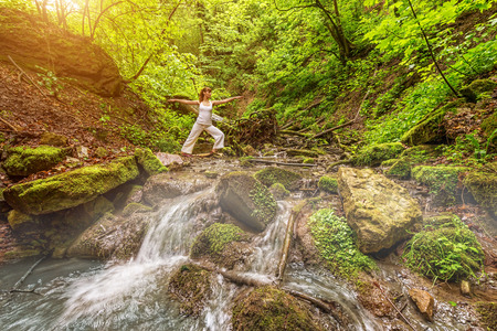 Relaxation joga  in forest at the Waterfall   Virabhadrasana pose