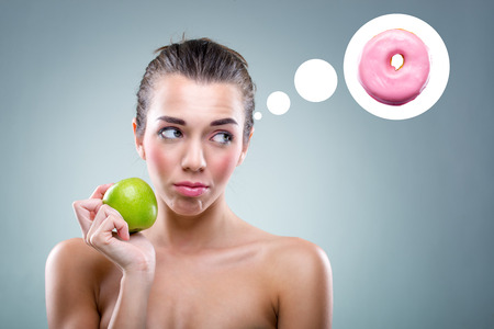 thinks:  The Diet  Woman eating an apple , but he thinks a donut