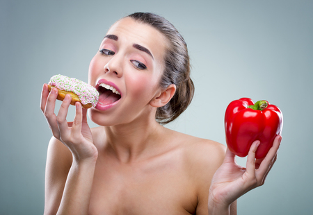 Women choosing between donut and vegetable Stock Photo