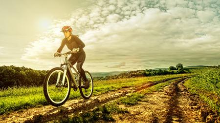 Sport bike woman on a meadow with a beautiful landscape photo