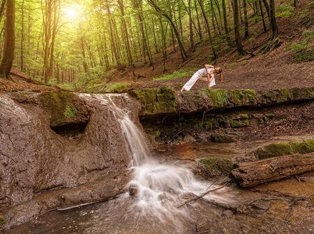 parsvakonasana: Woman practices yoga in nature, the waterfall  parsvakonasana pose