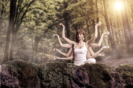 Eight arm woman sitting on a forest and pray photo