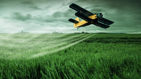 A crop dusting plane working over a field  Stockfoto