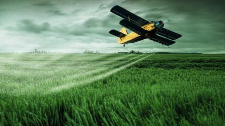 A crop dusting plane working over a field  Standard-Bild