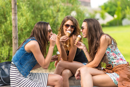 3 pretty woman eating ice cream in town, sitting on a bench, laughing  Stockfoto