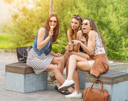 The best friends  Three beautiful woman eating ice cream in the City photo