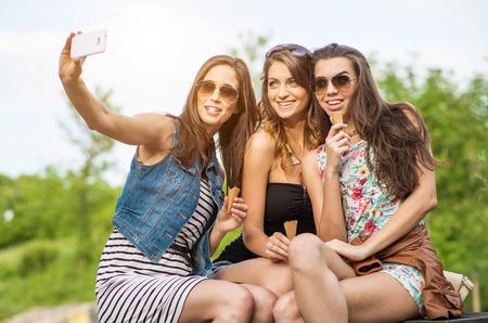 가장 친한 친구 Selfie -시에서 세 아름다운 여자 먹는 아이스크림 스톡 콘텐츠