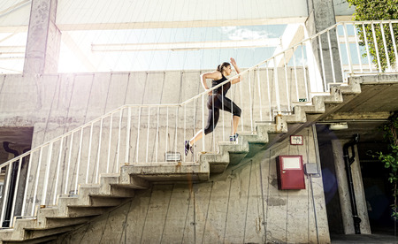city road: Running woman in black sports outfit, running up the stairs  Stock Photo