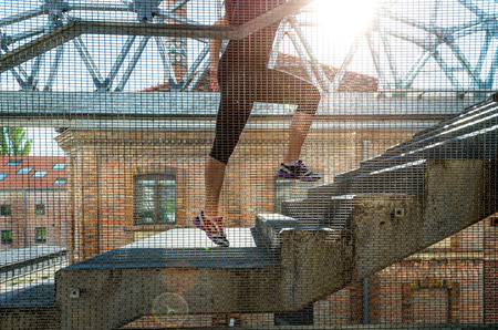 Running woman in black sports outfit, running up the stairs  Stock Photo