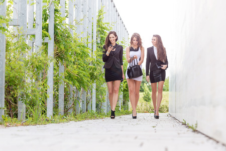 Three important and successful business woman walking down the street photo