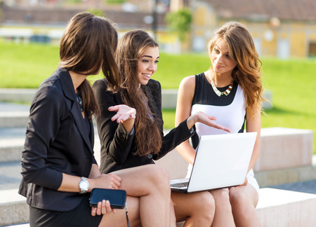 discussed: Three Successful businesswomen in the city on a bench discussed