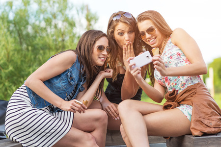 3 beautiful girlfriend watch the funny photos taken at  photo