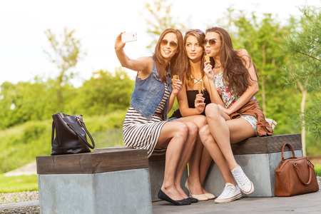 Three beautiful girlfriends make Selfie photo on a bench  photo