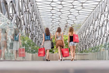 go shopping: 3 Pretty woman walking on the bridge, they go shopping - back photo  Stock Photo