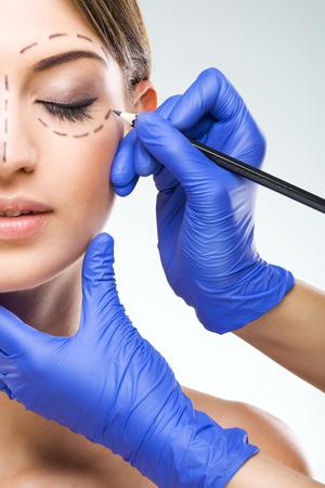 아름 다운 여자 절반 얼굴 사진 성형 수술, 성형 외과 의사 손 스톡 콘텐츠