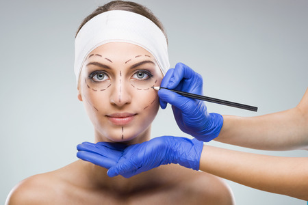 Beautiful woman with plastic surgery, depiction, plastic surgeon hands Stockfoto