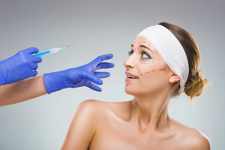 plastic glove: Beautiful woman with plastic surgery, the fear of the needle, a plastic surgeon hands  Stock Photo