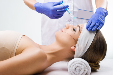 Beautiful woman lying in the clinic, a plastic surgeon in the hands of the needle  photo