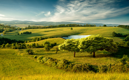 Beautiful hilly landscape with lake and blue cloudy sky Stock Photo