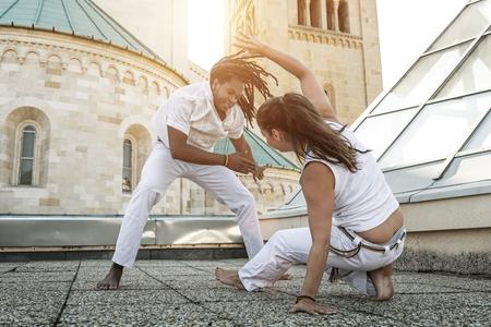 acrobatic: Young pair capoeira partners performing kicks outdoor Stock Photo
