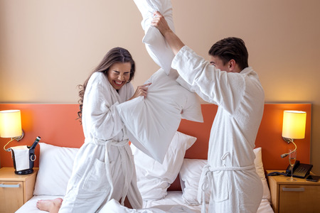 pillow fight: Happy Couple Having Pillow Fight in Hotel Room