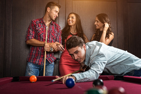 Fun with friends during playing billiard Foto de archivo