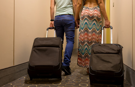 arriving: Young couple standing at hotel corridor upon arrival, looking for room, holding suitcases