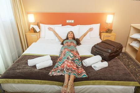 호텔 객실의 침대에 누워있는 젊은 여자