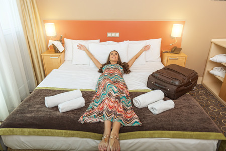 guest room: Young woman lying in the bed of a hotel room Stock Photo