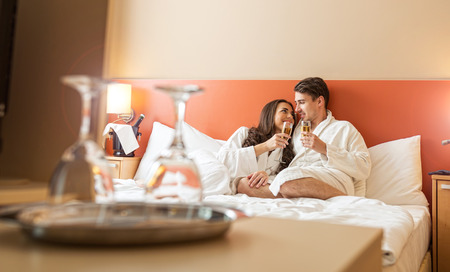 Smiling couple with champagne glasses in bed photo