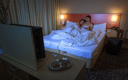 Young couple watching TV in the hotel room at night photo