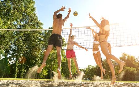 giovane donna: Gruppo di amici giovani giocano pallavolo sulla spiaggia