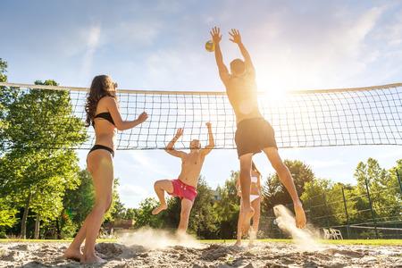 vacaciones playa: Grupo Amigos j�venes juegan a voleibol en la playa Foto de archivo