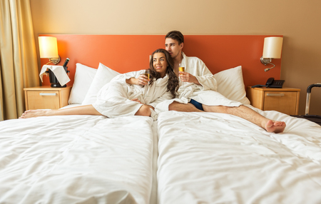 Young Couple lying in the bed of a hotel room photo