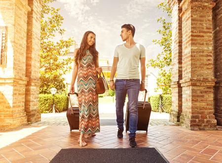Joven pareja de pie en el pasillo del hotel a su llegada, en busca de habitación, sosteniendo las maletas