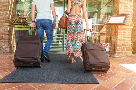 guest room: Young couple standing at hotel corridor upon arrival, looking for room, holding suitcases