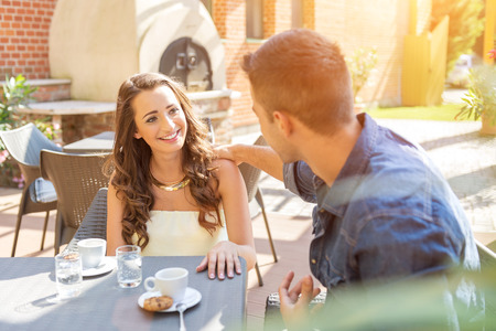 Young couple talking on the terrace of the restaurant, while eating