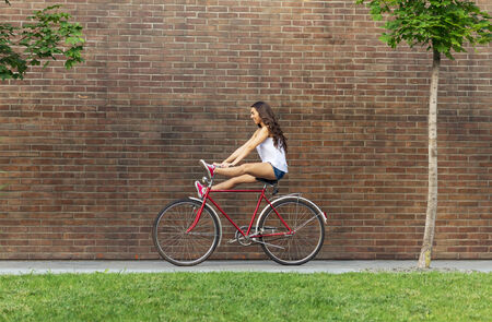 old bike: Beautiful woman with old bike in front of a brick wall